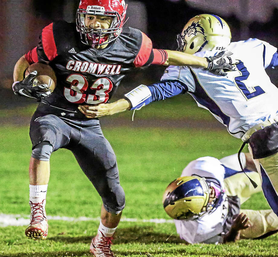 Cromwell's Kristian Sapp Skips out of the tackle attempt by Hyde's Tyrese Thomas during the Panther's 33-12 win over Hyde Friday evening in Cromwell Photo: Journal Register Co. / John Vanacore