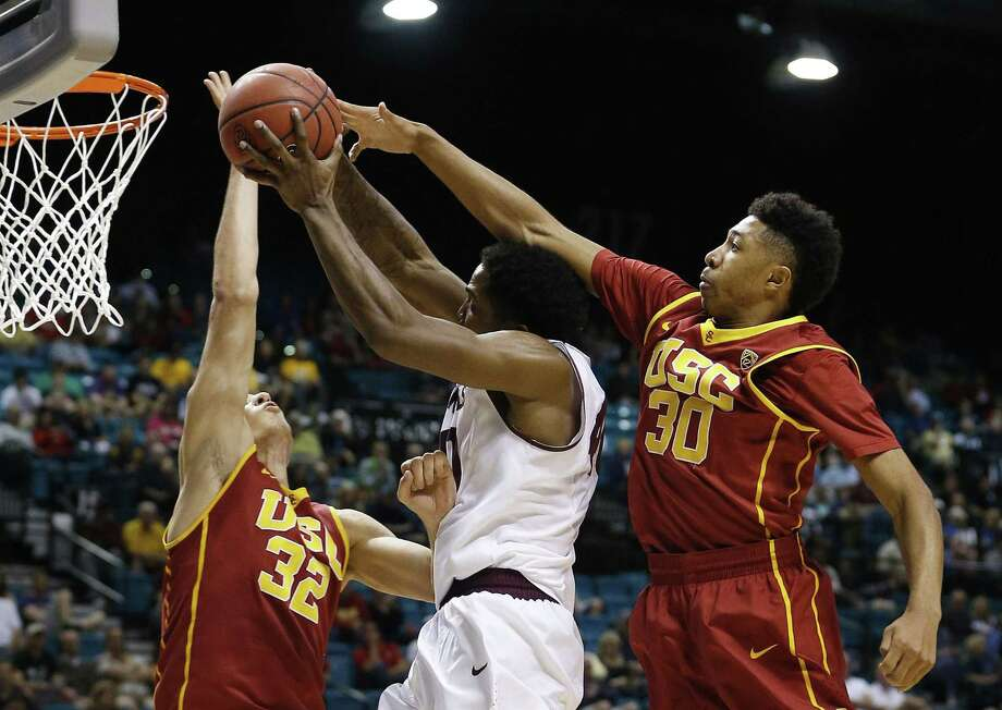 USC's Nikola Jovanovic, left, and Elijah Stewart, right, try to block Arizona State's Shaq McKissic during a first-round game of the Pac-12 tournament on Wednesday in Las Vegas. Photo: John Locher — The Associated Press  / AP