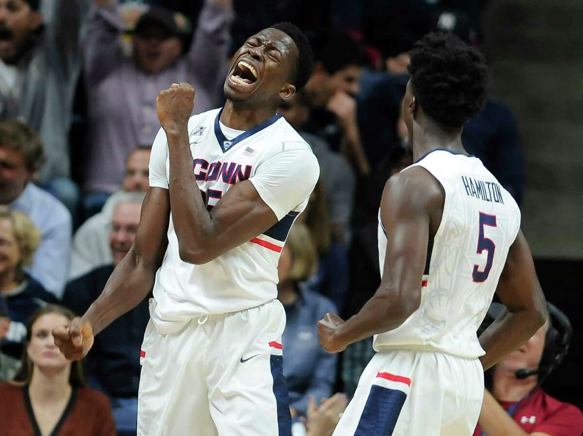 UConn's Amida Brimah, left, and Daniel Hamilton react after Brimah blocked a Maine shot in the first half of the Huskies' 100-56 win on Friday night in Storrs.