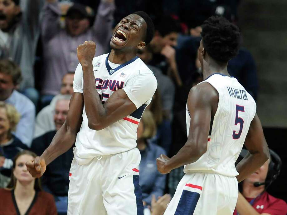 UConn's Amida Brimah, left, and Daniel Hamilton react after Brimah blocked a Maine shot in the first half of the Huskies' 100-56 win on Friday night in Storrs. Photo: Jessica Hill — The Associated Press  / FR125654 AP
