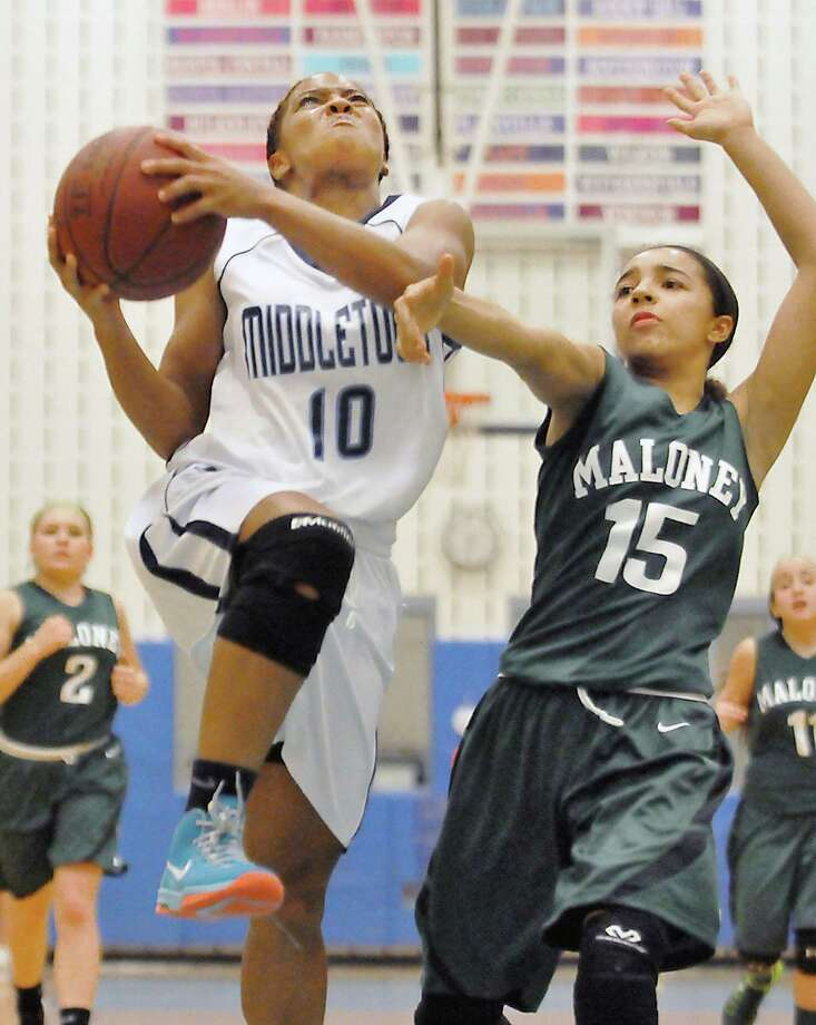 Middletown senior point guard Rejeen Mayo drives to the hoop as Maloney sophomore Jasmin Mitchell defends Friday night at the LaBella-Sullivan Gymnasium in Middletown. Mayo scored 16 for the night leading the Middletown Blue Dragons defeating the visiting Maloney Spartans, 61-29. Photo: Catherine Avalone — The Middletown Press  / TheMiddletownPress