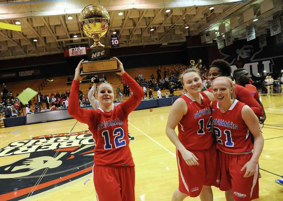 St. Francis (N.Y.) guard Leah Fechko (12) raises the trophy as teammates Sarah Benedetti (14) of Canton and Katie Fox (21) celebrate after defeating Robert Morris for the Northeast Conference tournament championship on Sunday in Moon Township, Pa. Photo: Don Wright — The Associated Press  / FR87040 AP