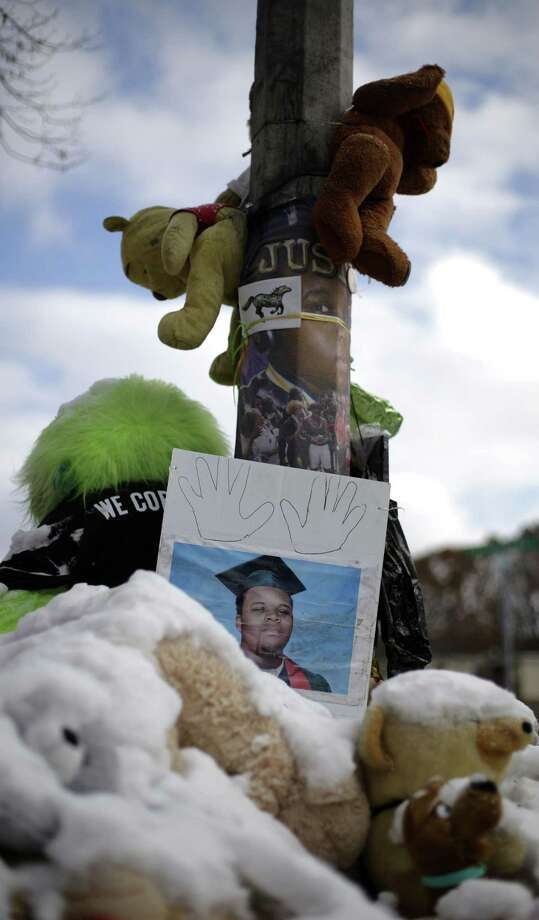A high school graduation photo of Michael Brown rests on top of a snow-covered memorial Monday, more than three months after the black teen was shot and killed nearby by a white policeman in Ferguson, Mo. The shooting sparked weeks of violent protests and  Missouri Governor Jay Nixon declaring a state of emergency today as a grand jury deliberates on whether to charge Ferguson police officer Darren Wilson in the death. Photo: Associated Press  / AP