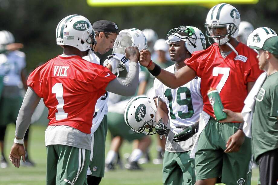 New York Jets quarterbacks Michael Vick (1) and Geno Smith (7) fist bump at training camp Thursday in Cortland, N.Y. Photo: The Associated Press  / AP