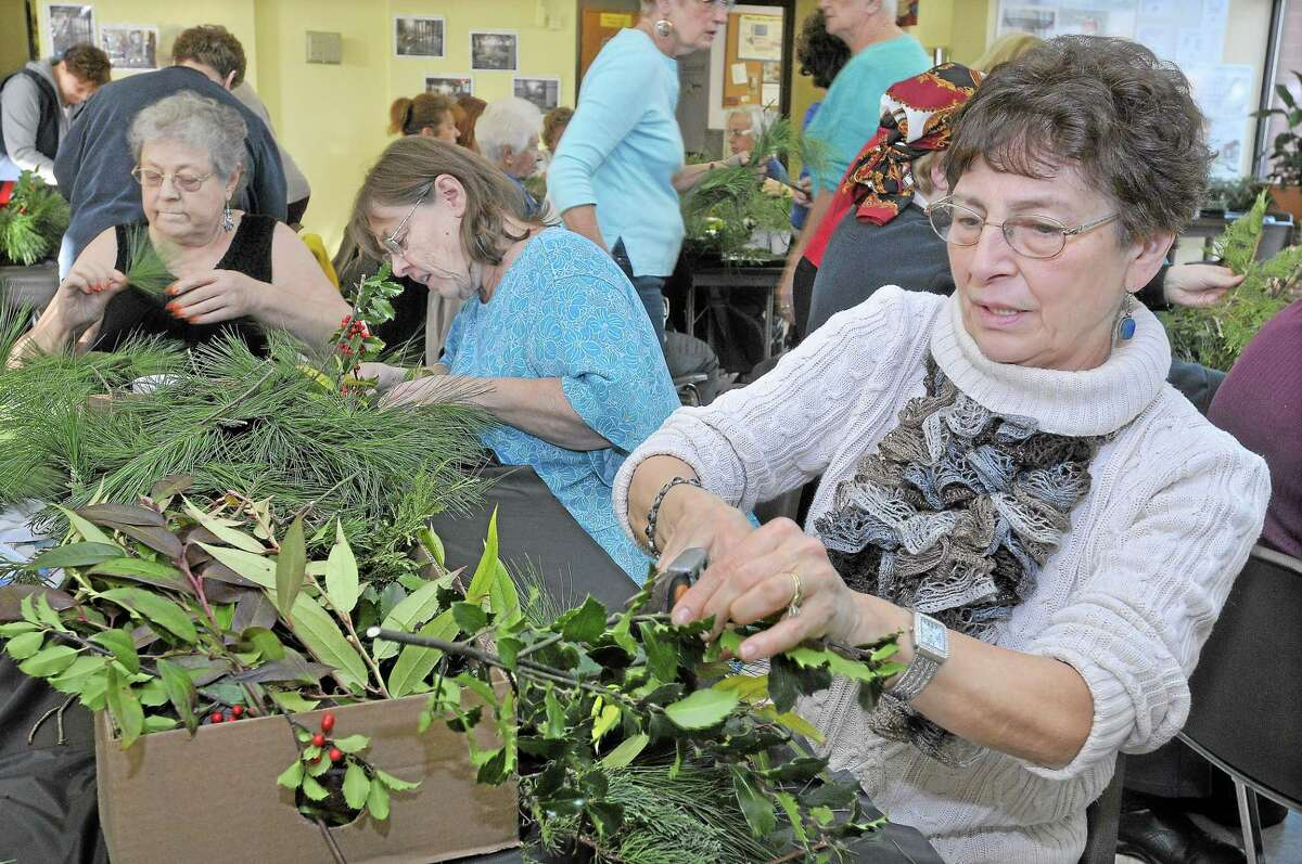 Susan Gombotz, Jane Koelsch and Chris Liebowitz, right to left, use fresh greens to create centerpieces during the Holiday Table Decorating Workshop sponsored by the Middletown Garden Club at the Middletown Senior Center in this file photo.