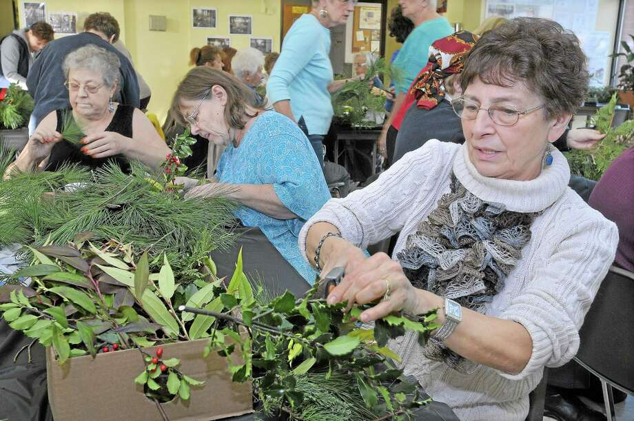 Susan Gombotz, Jane Koelsch and Chris Liebowitz, right to left, use fresh greens to create centerpieces during the Holiday Table Decorating Workshop sponsored by the Middletown Garden Club at the Middletown Senior Center in this file photo. Photo: File Photo  / TheMiddletownPress