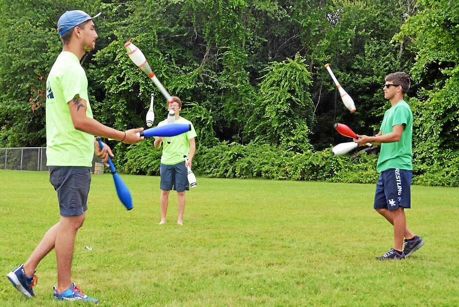 Photo by Julie Anne Rancourt Counselors, from left, Evan Knoll, Shane Keegan and Nick Adler demonstrate juggling with clubs during a break at the Children's Circus of Middletown camp. Photo: Journal Register Co.