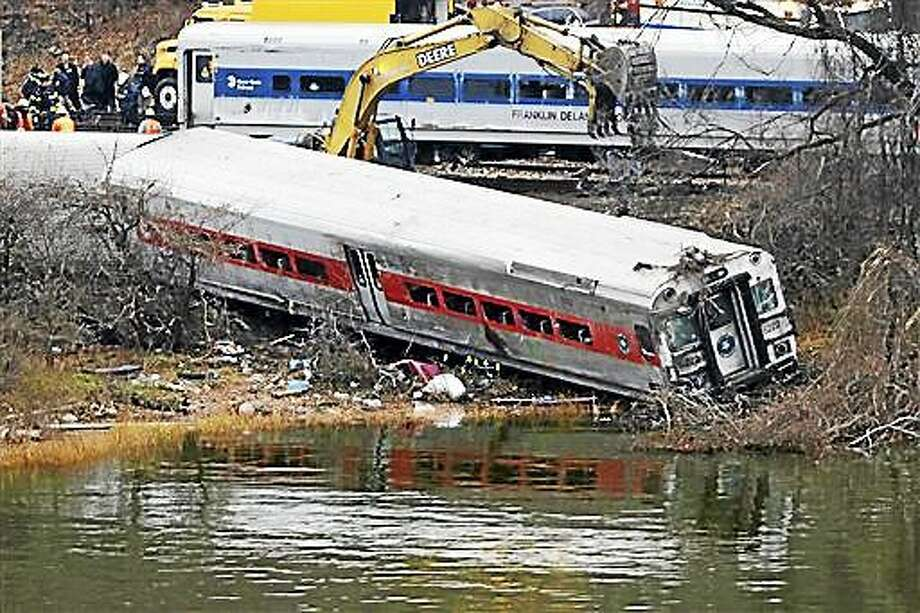 File-This Dec. 2, 2013, file photo shows a backhoe clearing soil next to a derailed Metro-North train car, foreground,  in the Bronx borough of New York. Photo: (AP Photo/Mark Lennihan, File) / AP