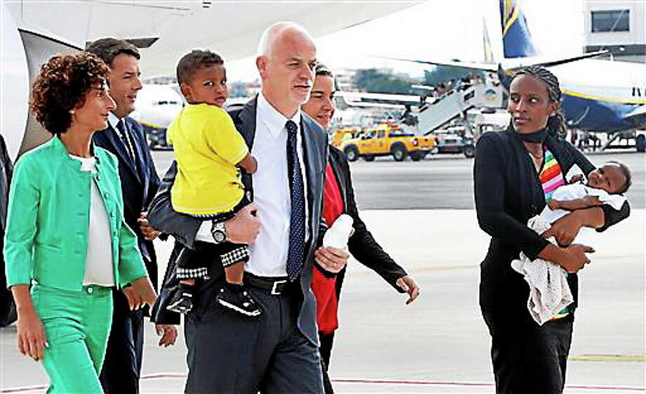Meriam Ibrahim, from Sudan, right, holds her baby girl Maya, accompanied by Italian deputy Foreign Miinister Lapo Pistelli, holding her son Martin, followed by Italian Foreign Minister Federica Mogherini, second from right, Italian Premier Matteo Renzi, second from left, and his wife Agnese Landini, after landing from Khartoum, at Ciampino's military airport, on the outskirts of Rome, Thursday, July 24, 2014. The Sudanese woman who was sentenced to death in Sudan for refusing to recant her Christian faith has arrived in Italy along with her family, including an infant born in prison. An Italian diplomat who accompanied the family from Sudan said Italy leveraged its historic ties within the Horn of Africa region to help win her release.  (AP Photo/Riccardo De Luca) Photo: ASSOCIATED PRESS / THE ASSOCIATED PRESS2014