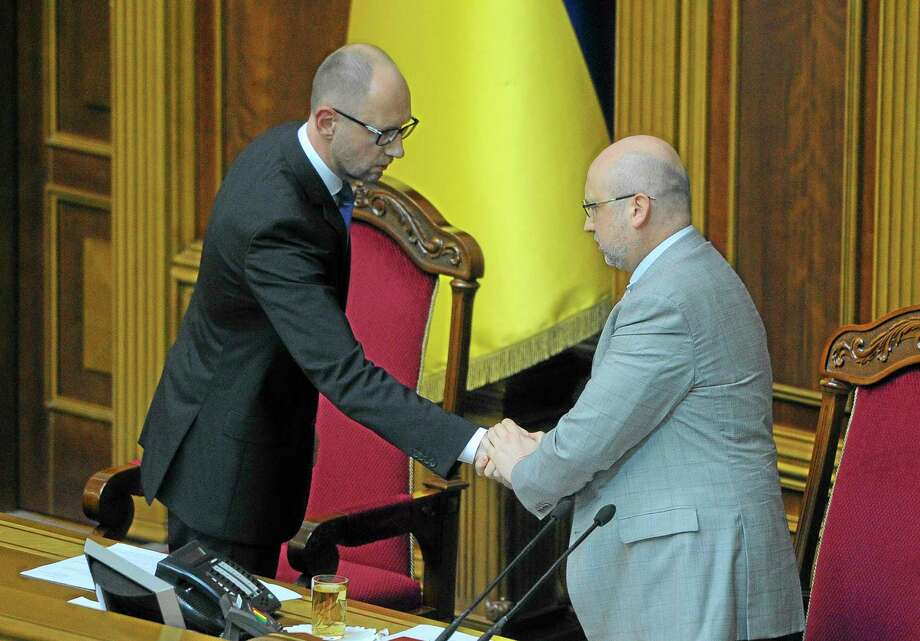 Ukrainian Prime Minister Arseniy Yatsenyuk, left, shakes hands with parliament speaker Oleksandr Turchynov after announcing his resignation in the parliament in Kiev, Ukraine, Thursday, July 24, 2014. Arseniy Yatsenyuk announced his resignation Thursday, a move that opens the way for new elections that would reflect countryís starkly changed political scene after the ouster of pro-Russian President Viktor Yanukovych in February. (AP Photo/Andrew Kravchenko, Pool) Photo: AP / Prime Minister Press Service