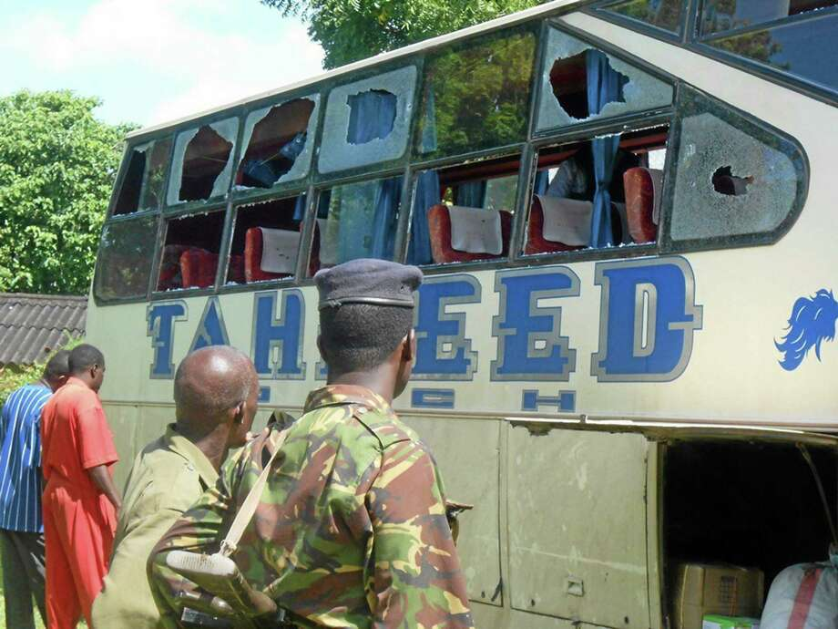 A Kenyan police officer with civilians watch the Taheed Bus at the Lamu Police Station, Saturday, July 19, 2014. The Kenya Red Cross says seven people have been killed after gunmen attacked a bus along the Kenyan coast where previous attacks had left 87 people dead. The humanitarian group said Saturday the attack Friday night came at Corner Mbaya, 5 kilometers (3 miles) from the coastal town of Witu. Al-Qaida-linked al-Shabab militants from Somalia claimed responsibility for the attack. (AP Photo) Photo: AP / AP