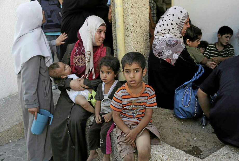 Displaced Palestinians grieve after an Israeli airstrike hit their pervious shelter of a U.N. school, at Beit Hanoun hospital in the northern Gaza Strip, Thursday, July 24, 2014. Israeli tank shells hit a compound housing a U.N. school in the Gaza Strip on Thursday, killing more than a dozen of people and wounding dozens who were seeking shelter from fierce clashes on the streets outside, Palestinian officials said, as Israel pressed forward with its 17-day war against the territory's Hamas rulers. (AP Photo/Adel Hana) Photo: AP / AP