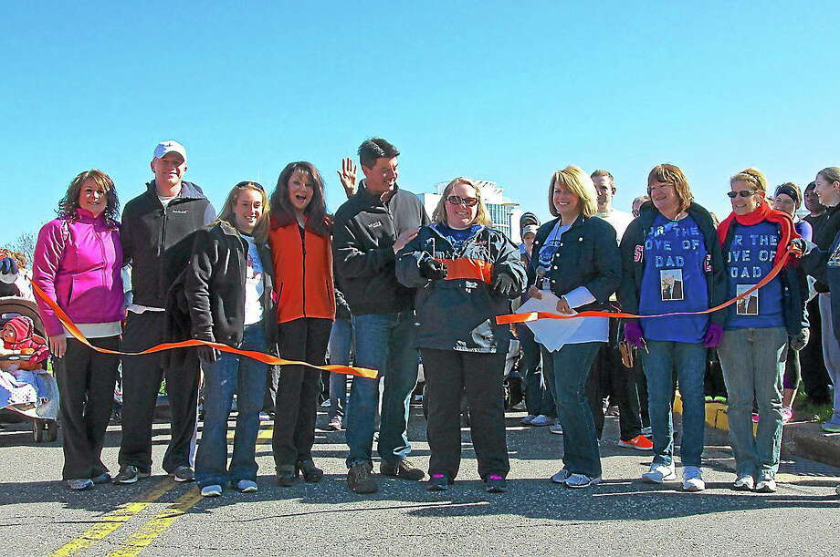 Darren Kramer, of Madison, and Renee DiNino, of Wethersfield, flank Willington resident Heidi Leetch as she cuts the ribbon at the start of the 2013 Walk MS in Manchester. Photo: Submitted Photo