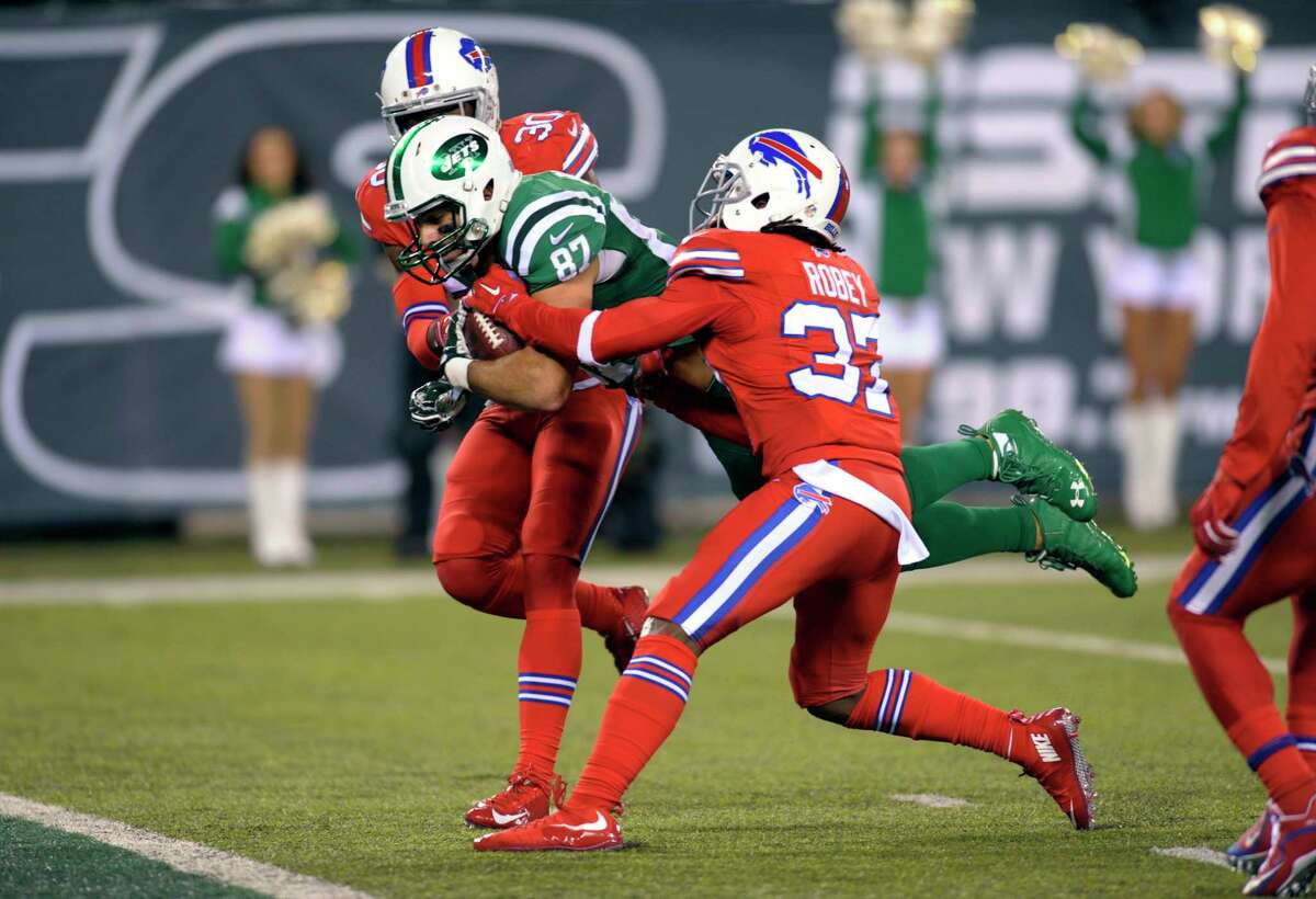 New York Jets wide receiver Eric Decker, center, scores on a touchdown catch as Buffalo Bills strong safety Bacarri Rambo, left, and defensive back Nickell Robey defend during the second half of an NFL football game, Thursday, Nov. 12, 2015, in East Rutherford, N.J. (AP Photo/Bill Kostroun)