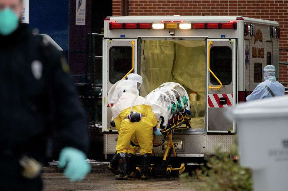 Health workers in protective suits unload Dr. Martin Salia, a surgeon working in Sierra Leone who had been diagnosed with Ebola, from an ambulance at the Nebraska Medical Center in Omaha, Neb., on Nov. 15, 2014. Photo: AP Photo/The World-Herald, Sarah Hoffman  / The World-Herald