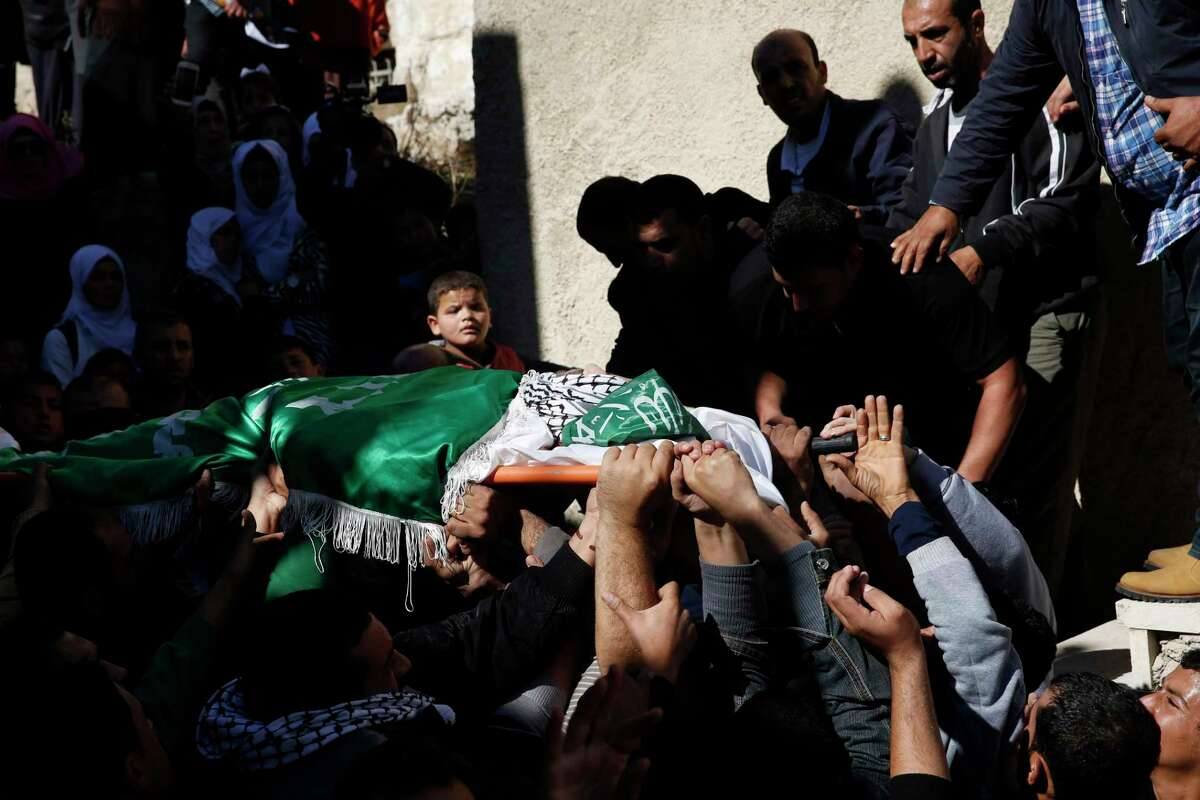 A Palestinian boy looks as mourners carry the body of 27-year-old Abdallah Shalaldeh, during his funeral in the West Bank village of Sa'ir, near Hebron, Thursday, Nov. 12, 2015. Israeli forces disguised in traditional Arab outfits, including one impersonating a pregnant woman and others appearing to have fake facial hair, burst into a hospital overnight Thursday, killing Shalaldeh during an arrest raid caught on video.