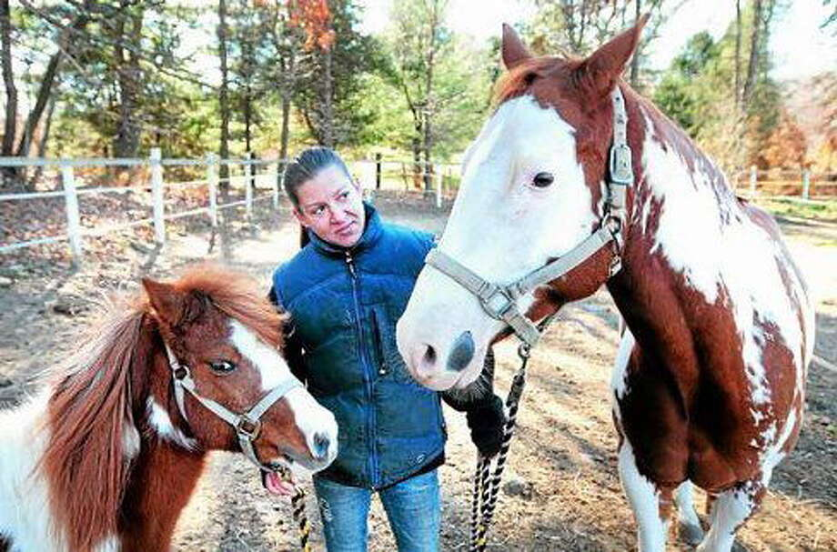 Shannon Pleines is photographed with a 14-year-old miniature pony, Sparkles, left, and Cash, right, a 6-year-old paint horse at Shannon Equine in Woodbridge in 2013. Photo: ARNOLD GOLD — NEW HAVEN REGISTER FILE PHOTO