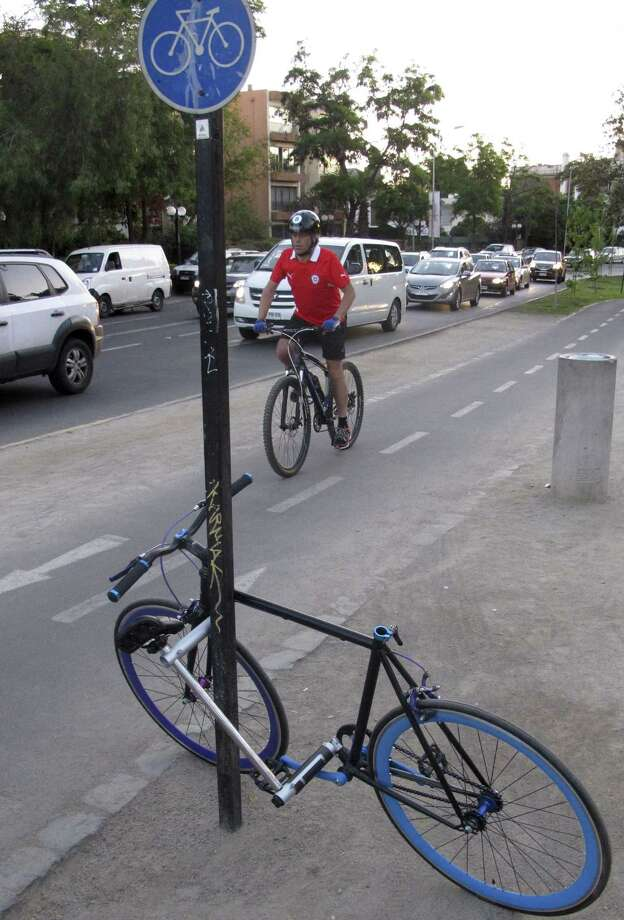"""In this Nov. 8, 2014 photo, a rider pedals on a bike trail next to the """"Yerka Project,"""" a prototype design for an """"unstealable bike"""" in Santiago, Chile. Commuters in Latin America and elsewhere have been taking advantage of the construction of designated cycling lanes, storage racks and bike share programs to ditch cars for bikes, which are cheaper and environmentally friendly. Photo: AP Photo/Luis Andres Henao  / AP"""