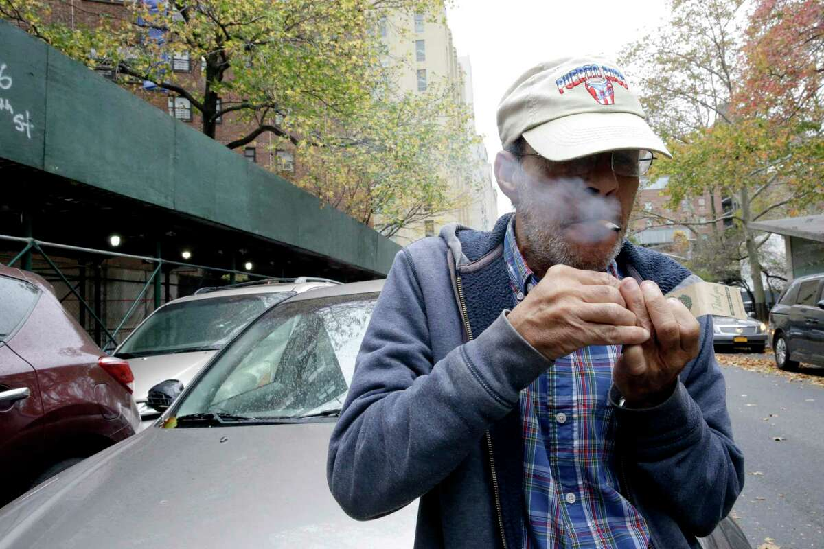 Luis Torres smokes a cigarette outside the New York City Housing Authority's Chelsea-Elliot Houses where he lives Thursday in New York.