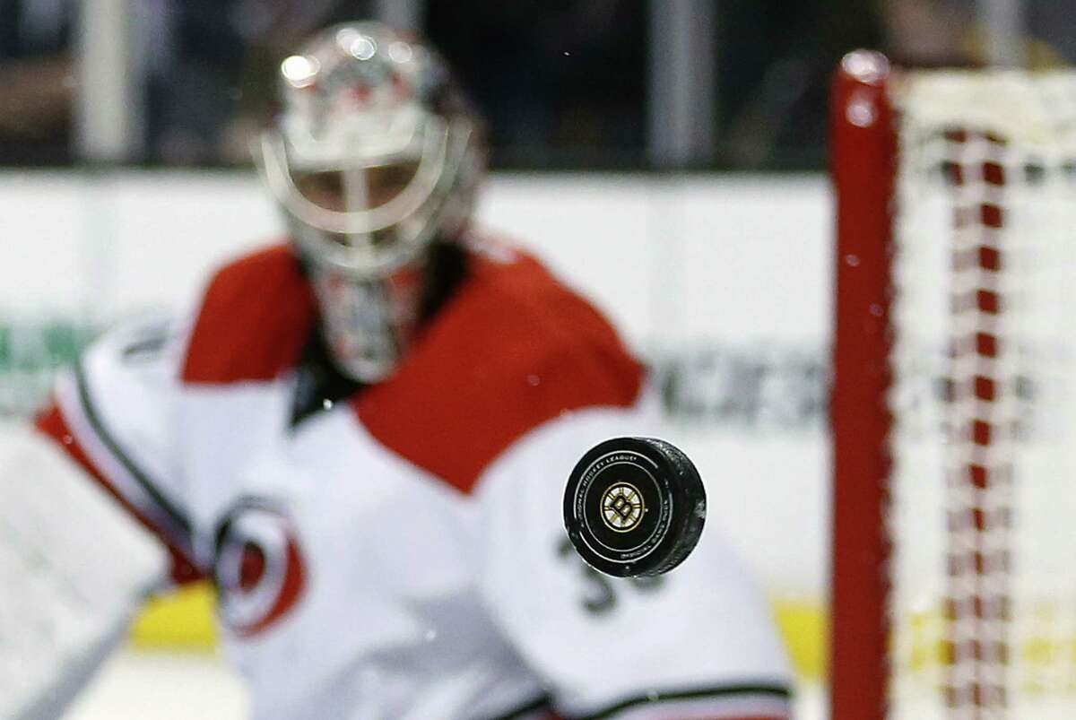 Carolina Hurricanes goalie Cam Ward watches as the puck goes wide of the net during the second period of the Bruins' 2-1 on Saturday afternoon in Boston.