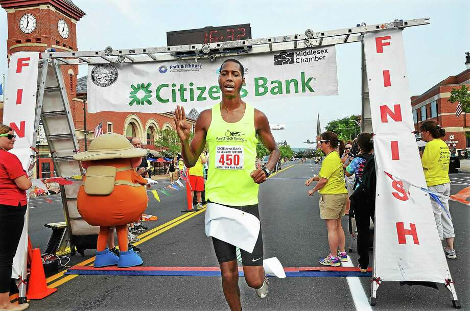 Middletown resident Rob Weston holds up four fingers indicating his fourth Citizens Bank 5K Summer Fun Run win with a 16:32 time in Middletown in 2014. Photo: File Photo