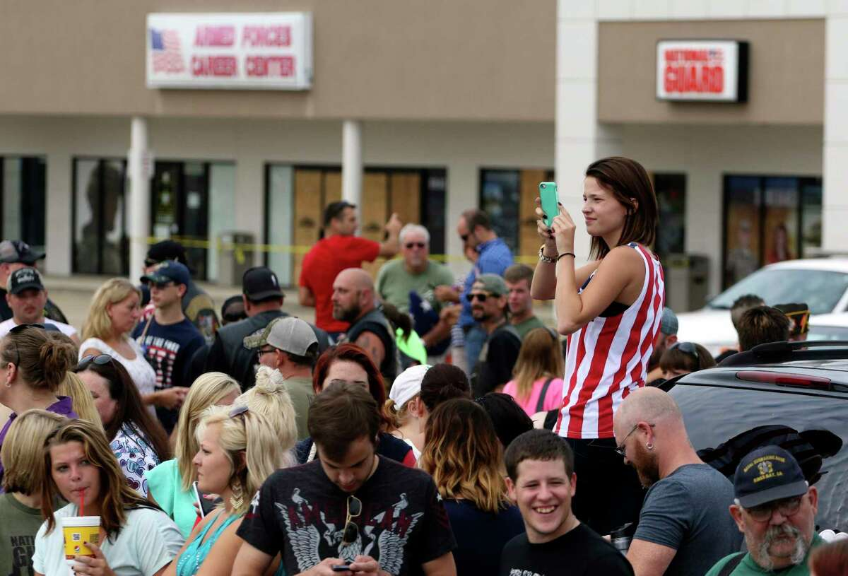 Ashlyn Moore stands on a car bumper Monday to take a photo of the large crowd that gathered at the Lee Highway memorial for last Thursday's Chattanooga, Tenn., shooting victims.