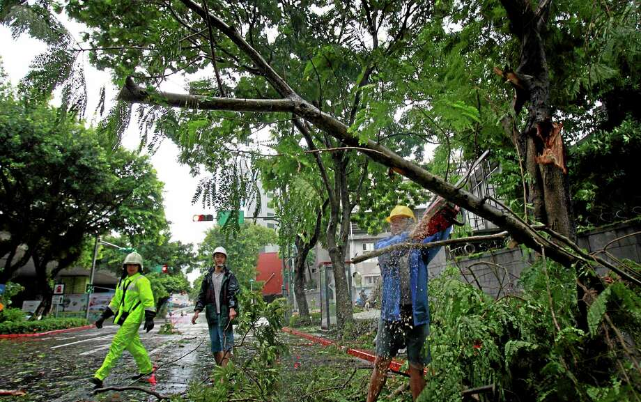 A city maintenance crew member removes fallen trees from a main road as Typhoon Matmo passes Taipei, Taiwan, Wednesday, July 23, 2014. The eye of Typhoon Matmo made landfall in eastern Taiwan early Wednesday bringing with it heavy rains and winds with gusts over 140 kilometers (85 miles) per hour. Photo: AP Photo/Wally Santana   / AP