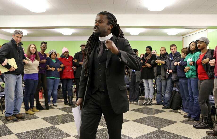 In this Wednesday, Nov. 12, 2014 photo, Rev. Osagyefo Sekou, a pastor from the First Baptist Church in Jamaica Plain, Mass., tells those assembled, at a protest training session in in St. Louis, Mo., that it is harder for police to make an arrest when people link arms together.  At least 600 potential Ferguson protesters have received training in the past week from a group of organizers who say theyíre stressing non-violence. A grand jury is considering whether Ferguson officer Darren Wilson should be charged in the Aug. 9 fatal shooting of Michael Brown. (AP Photo/St. Louis Post-Dispatch, J.B. Forbes) Photo: AP / St. Louis Post-Dispatch