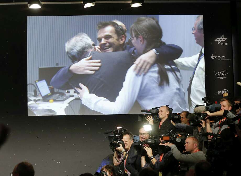FILE -In this Nov. 12, 2014 file picture celebrating scientists in the control room appear on a video screen at the European Space Agency ESA  after the Rosetta's  Philae landed on  comet  67P/Churyumov-Gerasimenko, in  Darmstadt, Germany. Philae landed next to a cliff that largely blocked sunlight from reaching its solar panels on the  comet. The head of the European comet mission says scientists will listen for signals from the Philae lander Saturday Nov. 15, 2014  but think it is unlikely they will establish any kind of communication soon. Controllers at the European Space Agency on Friday ordered the lander to perform a maneuver intended to pull it out of a shadow on  the comet so that solar panels could recharge the depleted batteries. ìWe donít know if the charge will ever be high enough to operate the lander again,î Paolo Ferri, ESAís head of mission operations, told The Associated Press.   (AP Photo/Michael Probst) Photo: AP / AP