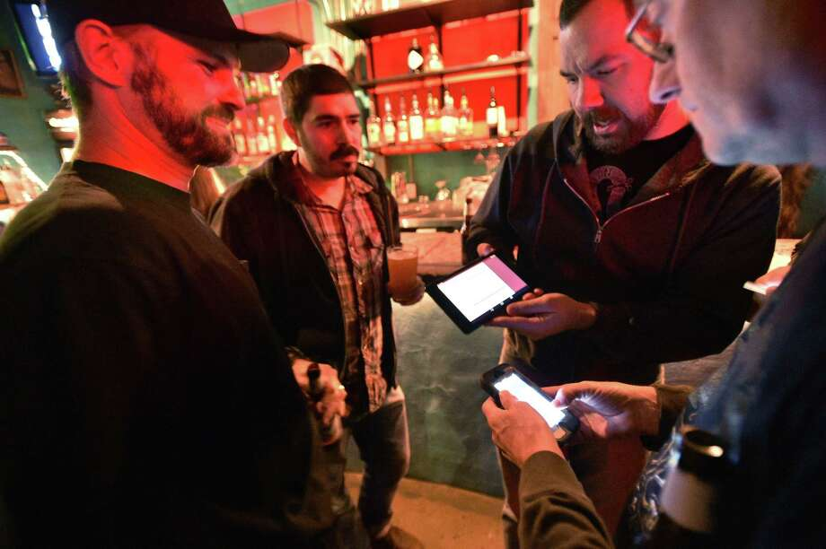 "Josh Berthume shows the election results website on a tablet at a nonpartisan election watch party at Dan's Silverleaf to see the results of propositions to ban hydraulic fracturing within the City of Denton and to remove the private club rules for alcohol sales and make Denton an officially ""wet"" city, Tuesday, Nov. 4, 2014, in Denton, Texas. Photo: The Associated Press — Denton Record-Chronicle, David Minton  / Denton Record-Chronicle"