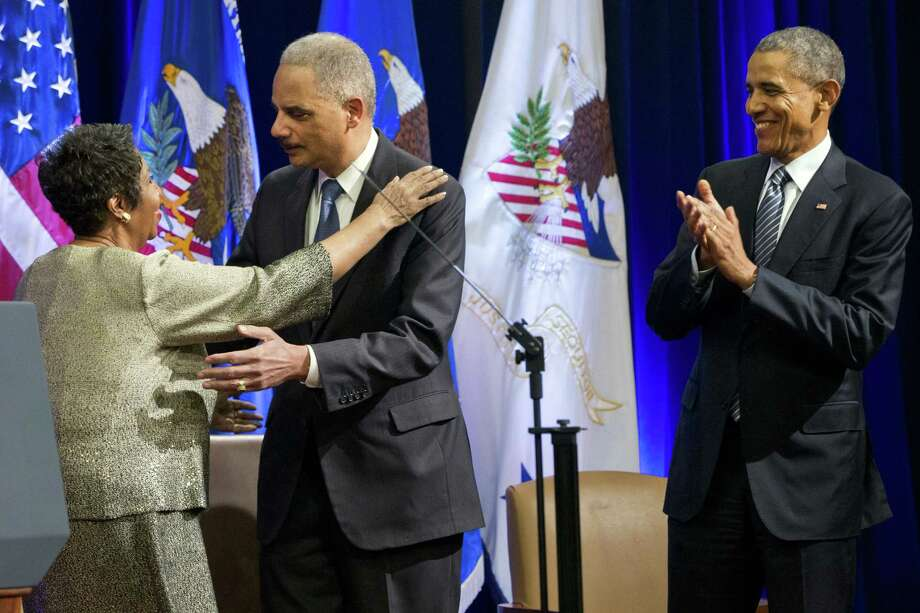 Singer Aretha Franklin, left, hugs outgoing Attorney General Eric Holder, as President Barack Obama applauds, at an event celebrating Holder at the Department of Justice in Washington on Feb. 27, 2015. Franklin. Photo: AP Photo/Jacquelyn Martin  / AP
