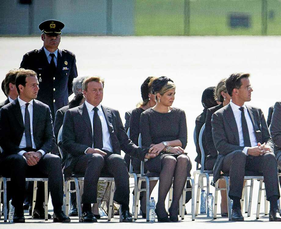 From left: Minister of Social Affairs Lodewijk Asscher, King Willem-Alexander, Queen Maxima and Prime Minister Mark Rutte attend a ceremony to mark the return of the first bodies, of passengers and crew killed in the downing of Malaysia Airlines Flight 17, from Ukraine at Eindhoven military air base, Netherlands, Wednesday, July 23, 2014. After being removed from the planes, the bodies are to be taken in a convoy of hearses to a military barracks in the central city of Hilversum, where forensic experts will begin the painstaking task of identifying the bodies and returning them to their loved ones. (AP Photo/Phil Nijhuis) Photo: AP / AP