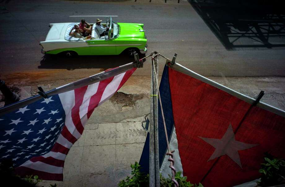 A U.S. and a Cuban national flag hang from a balcony to mark the restored full diplomatic relations between Cuba and the Unites States, in Old Havana, Monday. Photo: Ramon Espinosa — The Associated Press  / AP
