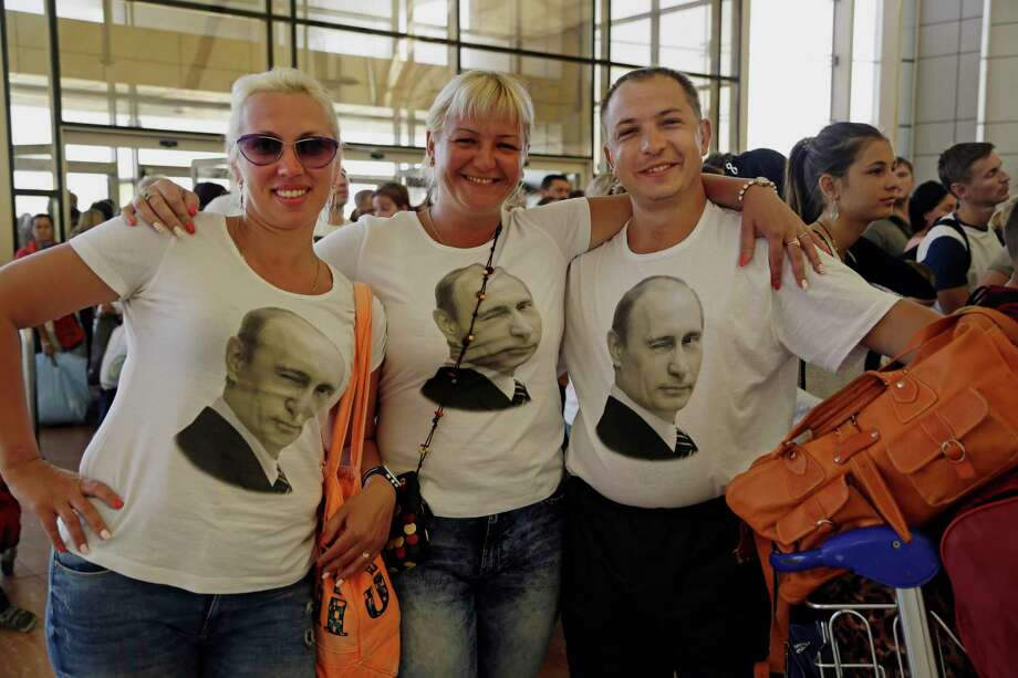 In this Friday, Nov. 6, 2015, file photo, Russian tourists wearing t-shirts with images of Russian President Vladimir Putin pose for a photo in the departure terminal before boarding a flight from Sharm el-Sheikh, south Sinai, Egypt. Egypt's benchmark stock index plunged 4.4 percent on Tuesday, Nov. 10, 2015, after steadily declining since Russia suspended flights to Egypt following the Oct. 31 Russian plane crash in the Sinai Peninsula. Photo: AP Photo/Thomas Hartwell, File   / AP
