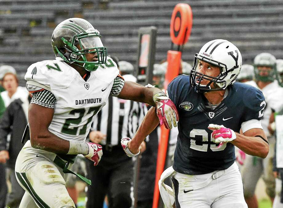 Yale senior Grant Wallace, here running alongside Dartmouth's Vernon Harris, is averaging over 100 yards per game receiving this season. Photo: Catherine Avalone — Register File Photo  / New Haven RegisterThe Middletown Press