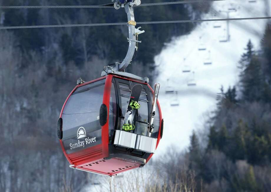 A snowboarder and skier ride the Chondola ski lift at the Sunday River ski resort, Friday, March, 13, 2015 in Newry, Maine. CNL Resort Properties , the real estate investment trust that's the largest owner of ski areas in the country, including Sunday River, is quietly putting the entire lot, along with dozens of other properties, up for sale. The company is looking to liquidate to repay investors. Photo: AP Photo/Robert F. Bukaty  / AP