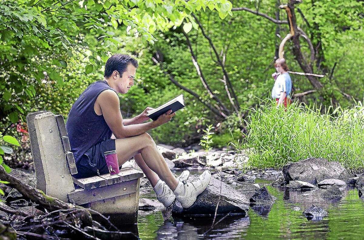 Chris Lucas of Meriden is reading at Wadsworth Falls in Middlefield. Lucas, who grew in Middlefield, is reading a fantasy book named Scar Night by Alan Campbell.