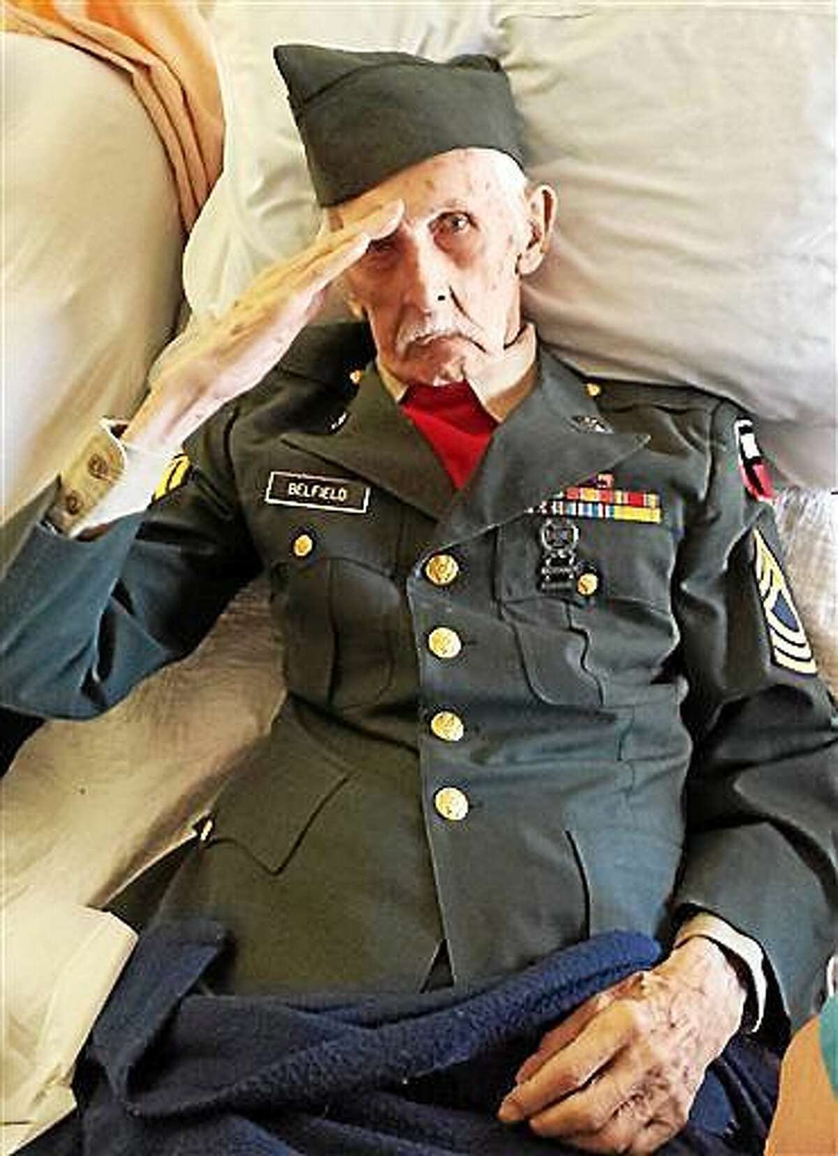 This Nov. 11, 2014 photo provided courtesy of Nancy McKiernan of Baptist Health Nursing and Rehabilitation Center in Glenville, N.Y., shows 98-year-old World War II veteran Justus Belfield saluting on Veterans Day. The Daily Gazette of Schenectady reports Belfield had worn his Army uniform every Veterans Day since he and his wife moved into the nursing home outside Albany several years ago. On Tuesday, the former master sergeant wasn't able to get out of bed to participate in the facility's Veterans Day festivities, so he had the staff dress him in his uniform. Belfield passed away the next day. (AP Photo/Courtesy of Nancy McKiernan/Baptist Health Nursing and Rehabilitation Center)