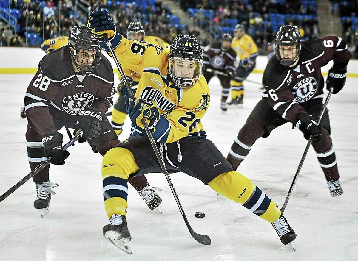 Quinnipiac's Travis St. Denis battles Union's Noah Henry (28) and David Roy (26) during the Dutchmen's 3-2 win on Saturday night in the second game of a best-of-3 ECAC Hockey quarterfinal series at High Point Solutions Arena in Hamden.