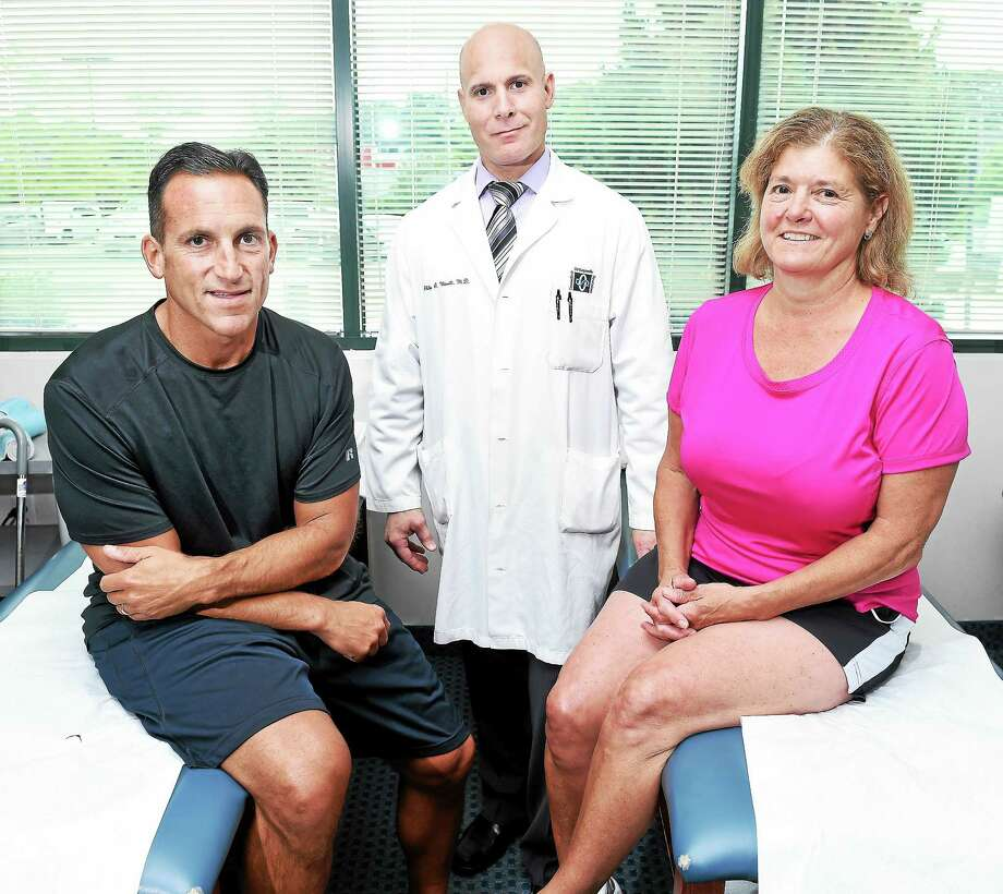 Orthopedic surgeon Dr. Philip Minotti (center) of Connecticut Orthopaedic Specialists is photographed with his patients Anthony Avallone (left) of Guilford and Karen Klarman-Williams of Branford last week. Minotti performed hip replacement surgery on the two. Photo: Arnold Gold--New Haven Register