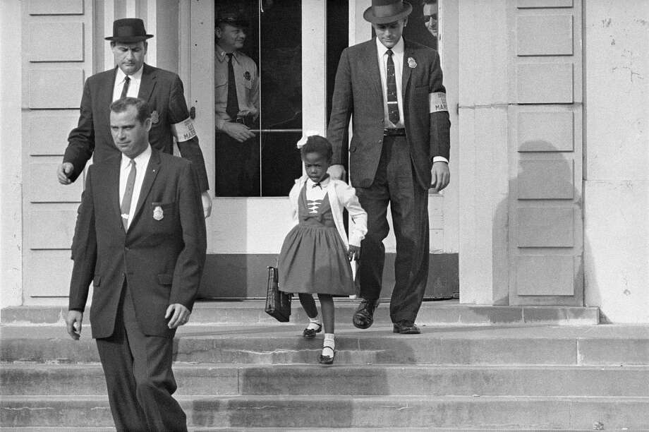 FILE - U.S. Deputy Marshals escort 6-year-old Ruby Bridges from William Frantz Elementary School in New Orleans, in this November 1960, file photo. On Friday, Nov. 14, 2014, 54 years later to the day when she first walked up the steps to the school, Bridges is scheduled to commemorate the event with the unveiling of a statue in her likeness on the campus. (AP Photo/File) Photo: AP / AP