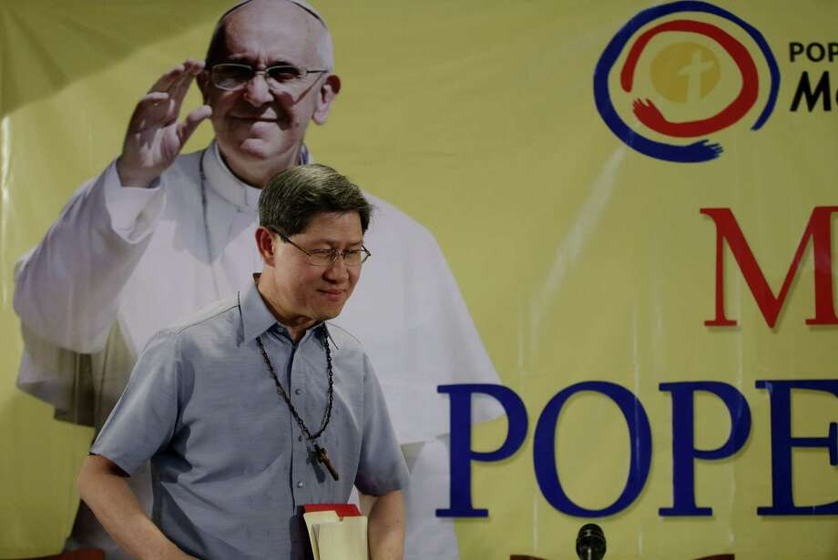 Manila Archbishop Cardinal Luis Antonio Tagle prepares to take his seat for a news conference Friday, Nov.14, 2014 in Manila, Philippines to announce the itinerary of Pope Francis on his first visit to the Philippines to the Philippines in January 2015. Francis will celebrate Mass and host a luncheon for Filipino survivors of the deadly Typhoon Haiyan during his Jan. 12-19 visit to Sri Lanka and the Philippines, his second visit to Asia in a year that confirms the region is a priority of his pontificate. (AP Photo/Bullit Marquez) Photo: AP / AP