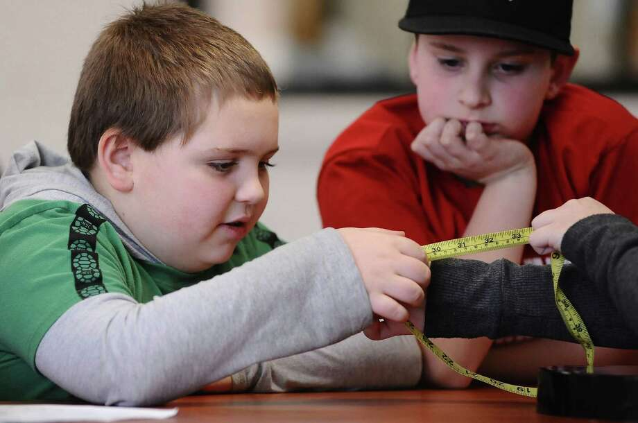 """Dustin Sponenberg, left, and Tanner Neidig, of the Southern Columbia Area School District, measure the circumference of an object Friday in order to calculate pi in Catawissa, Pa. """"Pi Day"""" is Saturday, when the date matches the first five digits of pi, 3.1415. Photo: (AP Photo/The News-Item, Larry Deklinski) / The News-Item"""