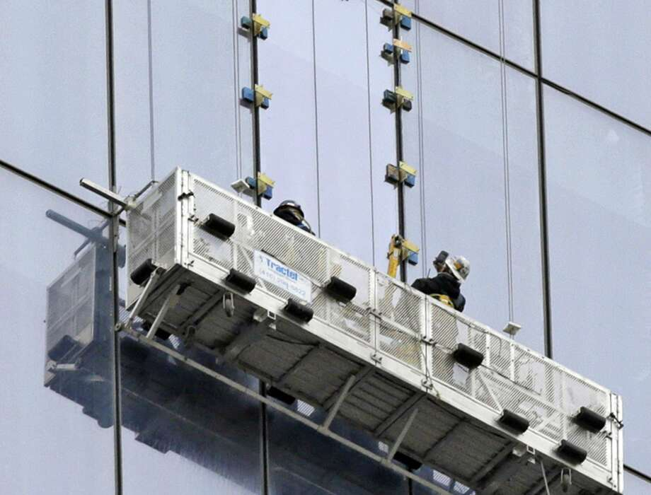 A worker, right, snaps a cell phone photo after replacing a window at 1 World Trade, Thursday, Nov. 13, 2014, in New York, the day after two window washers were rescued from a dangling scaffold by firefighters who cut through the pane to reach them.  (AP Photo/Kathy Willens) Photo: AP / AP