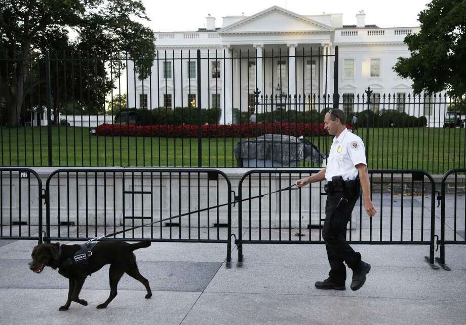 FILE - In this Sept. 22, 2014, file photo, a member of the Secret Service Uniformed Division with a K-9 walks along the perimeter fence along Pennsylvania Avenue outside the White House in Washington. Omar Gonzalez, 43, a knife-carrying Army veteran who scaled a White House fence and dashed into the executive mansion before being caught took a plea deal Friday, March 13, 2015. Gonzalez pleaded guilty to two federal charges. The Sept. 19 incident in which Gonzalez made it into the mansion's East Room preceded the disclosure of other serious Secret Service breaches in security for President Barack Obama and ultimately led to Julia Pierson's resignation as director of the agency. (AP Photo/Carolyn Kaster, File) Photo: AP / AP