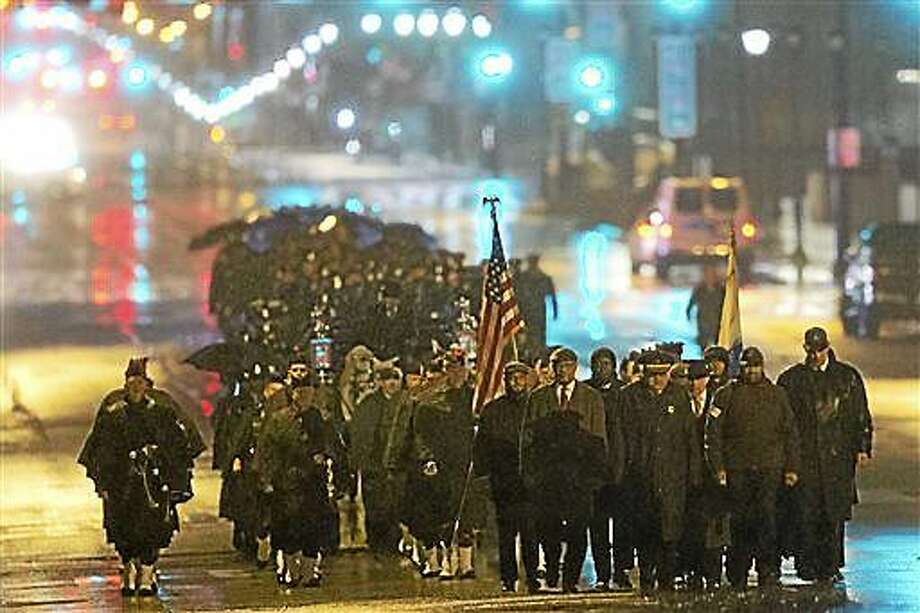 Philadelphia Police Officer Robert Wilson III funeral procession marches along Market Street during a winter rainstorm on Saturday, March 14, 2015, in Philadelphia. City officials said on March 5, 2015 Wilson was shot and killed after he and his partner exchanged gunfire with two suspects trying to rob a video game store.  (AP Photo/Matt Rourke) Photo: AP / AP