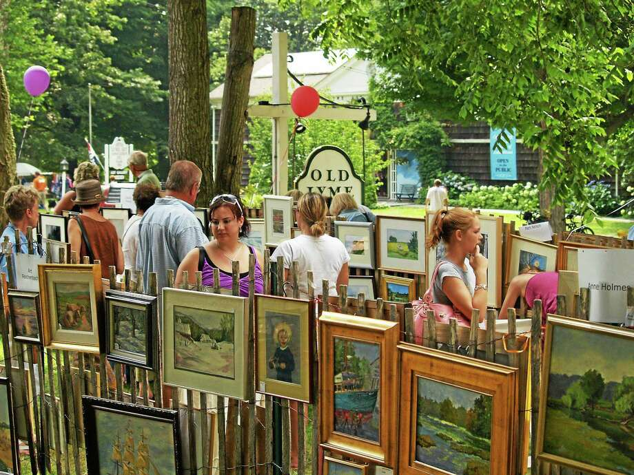Submitted photo Patrons admire the En Plein Air Painters' fence show at the Old Lyme Midsummer Festival. Photo: Journal Register Co.