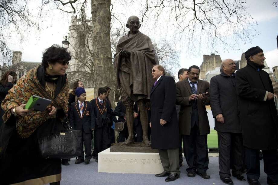 People stand around a new statue of Mahatma Gandhi by British sculptor Philip Jackson after it was unveiled in Parliament Square, London, Saturday, March 14, 2015.  The bronze sculpture stands 9ft-high (2.75m) and will provide a focal point for commemorations of the 70th anniversary of Gandhi's death in 2018. (AP Photo/Matt Dunham) Photo: AP / AP