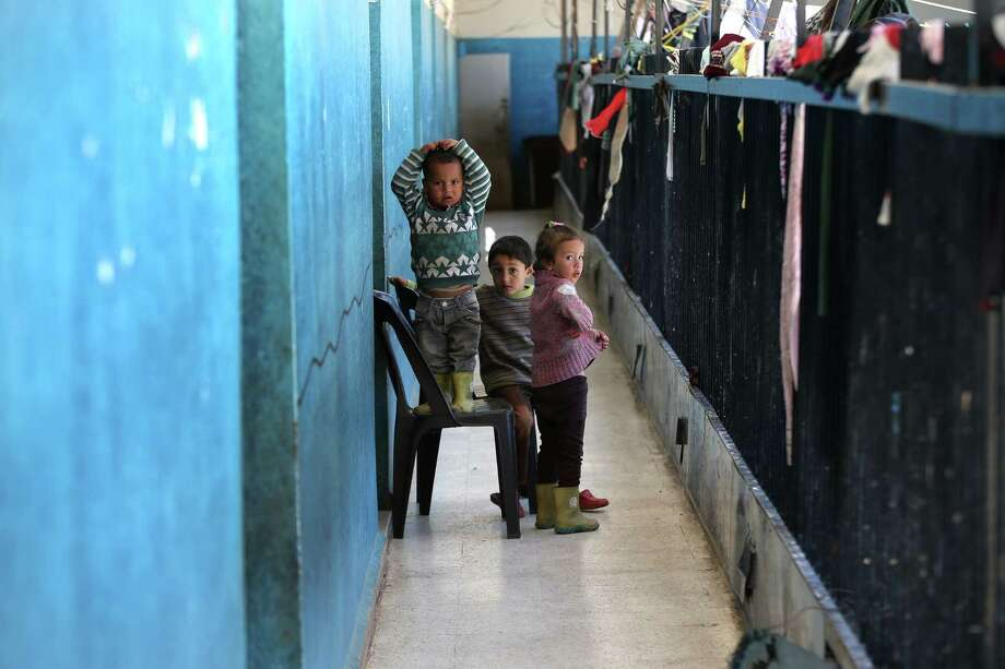 In this photo taken Friday, March 6, 2015, Syrian refugee children look at a photographer as they stand in the corridor at the Al-Rama Public School that become home to 22 Syrian families in Wadi Khaled in the Lebanese-Syrian border village of Al-Rama, north Lebanon. Now entering its fifth year, the Syrian civil war has claimed the lives of more than 220,000 people and displaced nearly half of the country's pre-war population of 23 million. (AP Photo/Hussein Malla) Photo: AP / AP