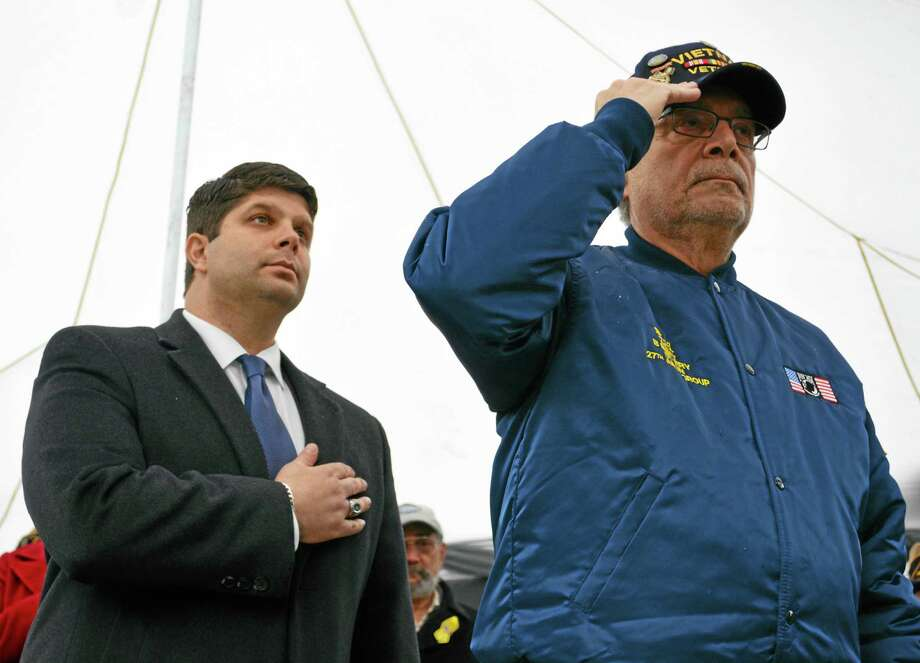 Middletown Mayor Dan Drew and Deputy Mayor and Common Councilman Robert Santangelo, who served in the Vietnam War, salute the flag at the State Veteran's Cemetery Veterans Day ceremony in Middletown. Photo: Cassandra Day — The Middletown Press